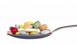 Macro of pills and capsules on a teaspoon