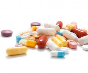 A choice of capsules and tablets on white background.